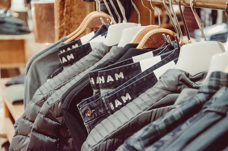 Kleidung für Männer auf Kleiderbügeln an einer Kleiderstange im Store von Modehaus Keller-Warth in Biberach