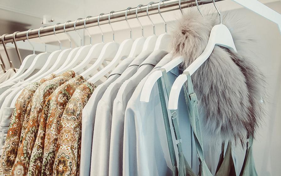 Kleidung für Damen auf einer Kleiderstange